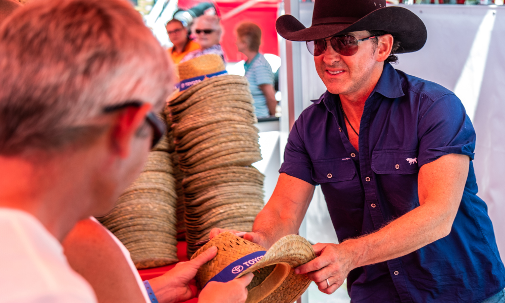 Lee Kernaghan signing hats as part of the traditional Toyota Country Music Festival hat give away